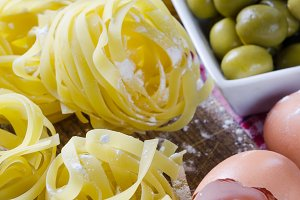 Uncooked pasta close up with olives.