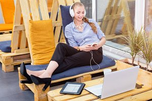 Pretty businesswoman is listening to music in modern loft. Freelance work, chill out and leisure concept. Woman in businness. Freelancer in coworking center is resting.