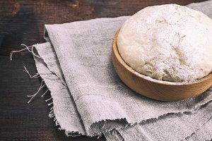 yeast dough in a wooden bowl