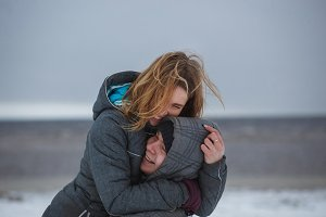 Happy moments of cheerful couple in winter near sea