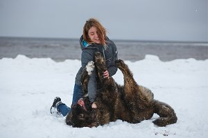 Happy woman playing with her dog on winter sea beach