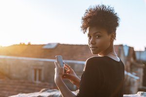 Black girl photographing using phone
