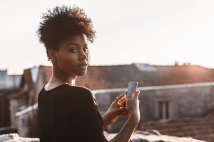 Black girl on roof with smartphone
