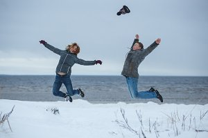 Young active couple joyful jumping up high together on winter holiday beach, nature outdoors. Fun energy recreational lifestyle, enjoying travel vacations.