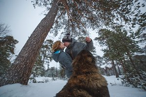 Young couple in love with dog walking in the snowy pine forest and kissing