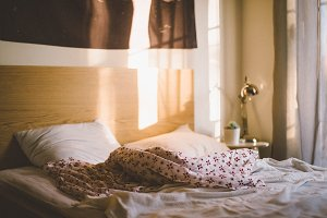 Messy bed in golden afternoon light