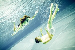 Underwater View Of A Young Couple Swimming