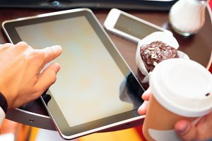 Businessman Sitting In A Cafe, Working On His Tablet