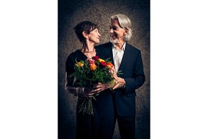 Senior Married Couple With Bouquet Of Roses