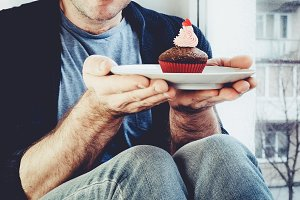 Handsome man sitting on a windowsill holding a plate with a cupcake