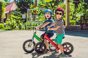 Two little boys children having fun on Balance Bike on a country tropical road