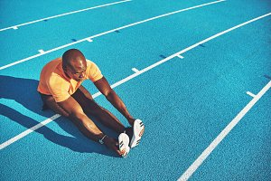 Young athlete stretching on a running track before training