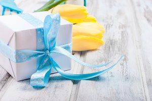 Gift box with a blue ribbon and bouq
