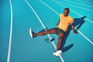 Young athlete relaxing on running track lanes before training