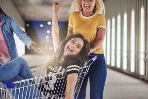 Young women pushing their laughing friend in a shopping cart