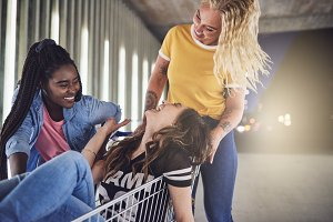 Laughing girlfriends having fun with a shopping cart at night