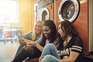 Friends using a cellphone on the floor of a laundromat