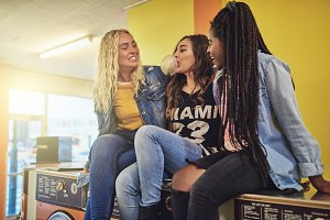 Girlfriends sitting on washing machines at a laundromat chewing bubblegum