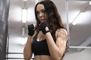 Beautiful Kickboxing woman training punching bag in fitness studio.