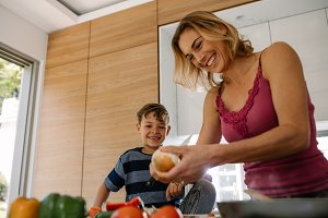 Happy mother and son preparing food
