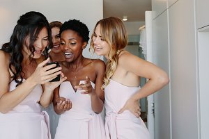 Bridesmaids using mobile phone
