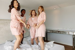 Bride and bridesmaids jumping on bed