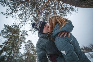 happy young beautiful couple kissing under the pine tree in snowy winter forest