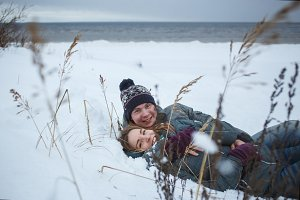Cheerful young couple lying in snow near se beach. Winter romanctic holiday