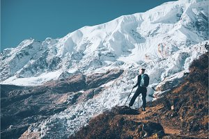 Woman with backpack on the mountain peak