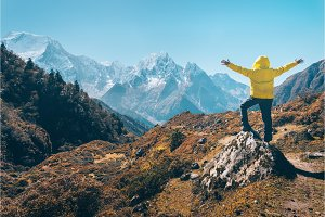 Standing man on the stone against snowy mountains