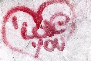 Cracked red heart on concrete wall