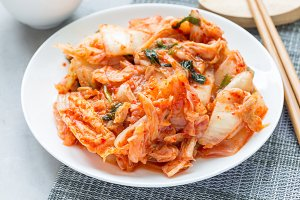 Kimchi cabbage. Korean appetizer on white plate, horizontal