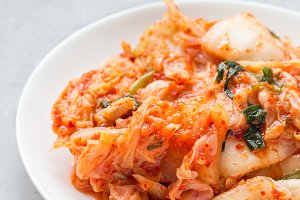 Kimchi cabbage. Korean appetizer on white plate, vertical, copy space