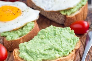 Making open sandwiches with mashed avocado and fried egg on bread, vertical