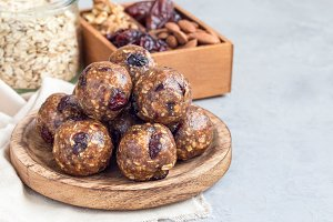 Healthy homemade energy balls with cranberries, nuts, dates and rolled oats on wooden plate, horizontal, copy space