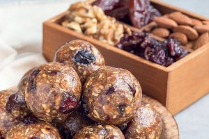 Healthy homemade energy balls with cranberries, nuts, dates and rolled oats on a wooden plate, vertical, copy space