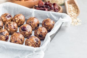 Healthy homemade energy balls with cranberries, nuts, dates and rolled oats, horizontal, copy space