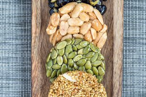 Korean traditional sweet snacks with peanuts, pumpkin seeds, black soybeans and chinese buckwheat. Healthy energy snacks. Top view, vertical