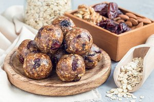 Healthy homemade energy balls with cranberries, nuts, dates and rolled oats on wooden plate, horizontal