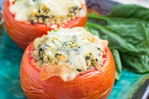 Baked tomatoes stuffed with quinoa and spinach topped with melted cheese on ceramic plate, square