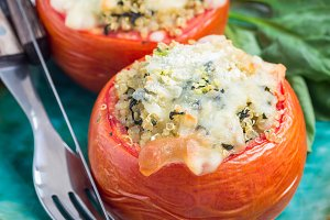 Baked tomatoes stuffed with quinoa and spinach topped with melted cheese on ceramic plate, square format