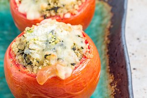 Baked tomatoes stuffed with quinoa and spinach topped with melted cheese on a ceramic plate, square format