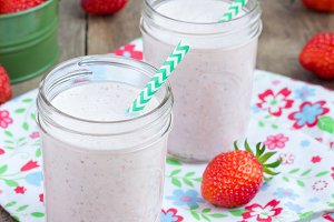 Healthy smoothie with strawberry, banana and yogurt in glass jar, square