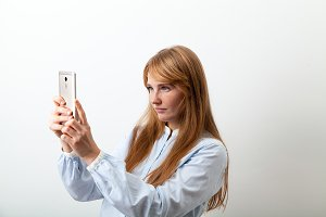 Horizontal headshot of young european lady with red hair, white skin and freckles holding her phone
