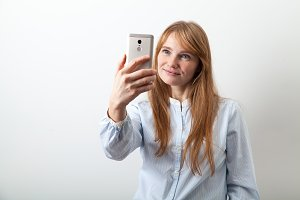 Horizontal headshot of young european lady with red hair, white skin and freckles making selfie
