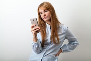 Horizontal headshot of young european lady with red hair, white skin and freckles dressed in casual blue shirt holding her phone