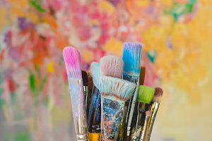 Paint brushes and colorful canvas
