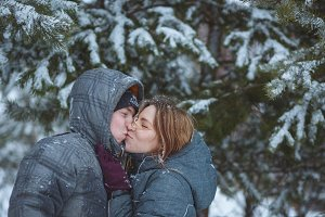 Happy snow covered couple kissing under fir branches in winter forest. Concept healthy romantic holidays on fresh air