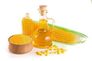 Corn oil in decanter, fresh corn cobs and cornmeal isolated on white background