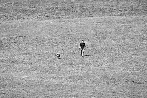 Man walking a dog in empty field